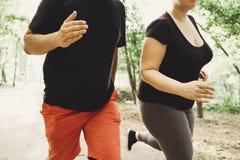 Förlorande vikt för överviktiga par som tillsammans kör arkivfoto
