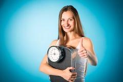 Förlorande vikt - ung kvinna med att mäta skalan Royaltyfria Bilder