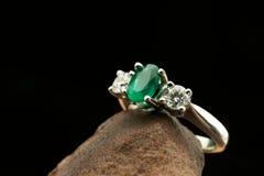 Förlovningsring med diamanter och smaragden Arkivfoto