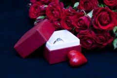 Förlovningsring med röda ro Arkivbild
