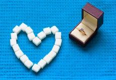 Förlovningsring- och sockerhjärtor royaltyfri foto