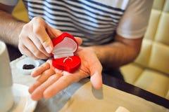 Förlovningsringar i händerna av en man i kafét Arkivfoto