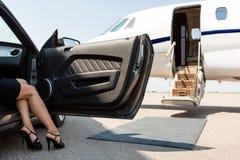 Förmögen kvinna som kliver ut ur bilen på terminalen Royaltyfri Foto