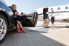 Förmögen kvinna som kliver ut ur bilen på terminalen Arkivbilder