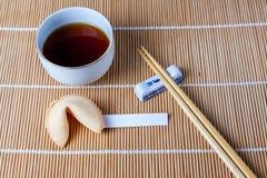 Förmögenhetkaka med snedsteget och pinnar och te Arkivfoton