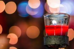 Förmögenhetstearinljus i den glass koppen Arkivbild
