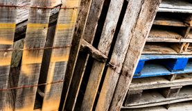 Förmultna träasken och staplade paletter med målarfärg och ålder Arkivbild