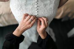 förnämsta brudtärna som hjälper bruden med hennes klänning Royaltyfria Bilder