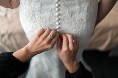 förnämsta brudtärna som hjälper bruden med hennes klänning Arkivbild