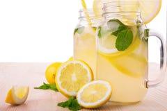 Förnya dricker med mogna, saftiga och nya citroner som är ljusa - den gröna mintkaramellen och mineralvatten som isoleras på en v Royaltyfri Fotografi
