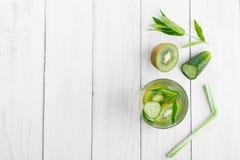 Förnyande drink för detoxification, mineralvatten i ett exponeringsglas, ny grön kiwi, mintkaramell och gurka på en vit tabell arkivfoto