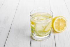 Förnyande drink för hälsa, citronvatten i ett exponeringsglas och gula lindblommor på en vit tabell arkivfoton