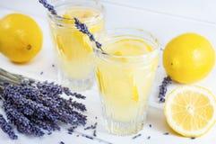 Förnyande lavendellemonad i exponeringsglas på vit träbakgrund royaltyfri foto