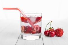 Förnyande vatten från röda bär i ett exponeringsglas på trätabellen Hemlagade smakliga och sunda drinkar royaltyfria bilder
