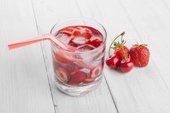 Förnyande vatten från röda bär i ett exponeringsglas på trätabellen Hemlagade smakliga och sunda drinkar arkivfoton