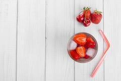 Förnyande vatten från röda bär i ett exponeringsglas på trätabellen Hemlagade smakliga och sunda drinkar arkivbild