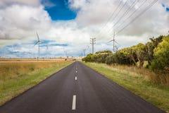 Förnybara energikällorvind maler turbiner i lantgårdfält längs vägen royaltyfria bilder