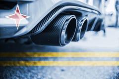 Förorening av miljön vid brännbar gas av en bil med att blanda den Aruba flaggan Arkivbild