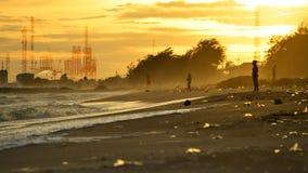 Föroreningbranschbegrepp, strandförorening Plast-flaskor och annat avfall på havsstranden och fabriksröret som förorenar luft mot Royaltyfri Foto
