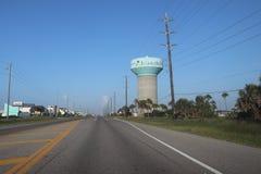 Förorts- Amerika, Texas, Förenta staterna Perspektivlandskapsikt av en väg, huvudvägen med vattentornet och maktpoler royaltyfria foton