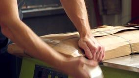 Förpackande möblemangprodukter N?rbild Arbetaren slår in försiktigt möblemangobjekten i papp som förpackar, förbereder sig lager videofilmer