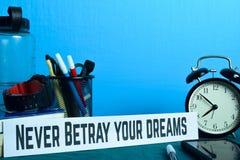Förråda aldrig dina drömmar som planerar på bakgrund av arbetetabellen med kontorstillförsel royaltyfri foto
