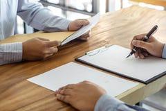 Försäkring- eller lånfastigheten, medelmäklaren och undertecknande avtalsöverenskommelse för klient som godkändes för att köpa eg royaltyfri bild