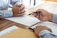 Försäkring- eller lånfastigheten, medelmäklaren och undertecknande avtalsöverenskommelse för klient som godkändes för att köpa eg arkivbild