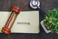 FÖRSÄKRING för ordkvarter på den gula boken över träbakgrund arkivfoton