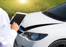 Försäkringmedel Inspecting Damaged Car med försäkringreklamationsformen på den Digital minnestavlan Royaltyfri Foto