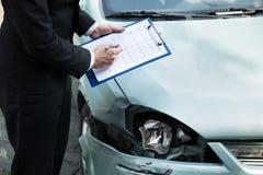 Försäkringmedel som kontrollerar bilen efter olycka Arkivbild