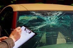 Försäkringmedel som skriver på skrivplattan, rapportbilolycka royaltyfria bilder