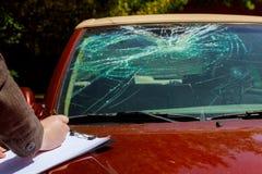 Försäkringmedlet beräknar kostnaden av den skadade bilen efter sammandrabbning med en hjort arkivfoto