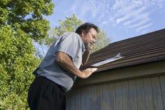 Försäkringregulator på mobiltelefonen som söker efter hagelskada Royaltyfri Fotografi