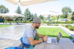 Försäkringsstatistiker som arbetar med bärbara datorn och legitimationshandlingar på kafétabellen Royaltyfri Fotografi