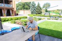 Försäkringsstatistiker som arbetar med bärbara datorn och legitimationshandlingar på kafétabellen Royaltyfria Foton
