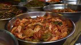försäljare 4K säljer Kimchi som används i koreansk kokkonst Shoppa i den Jagalchi marknaden Busan arkivfilmer