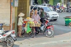 Försäljare med hennes cykel som är fullastad med grönsaker på CR Arkivfoton