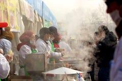 Försäljare som säljer det kinesiska mellanmålet till kunder i en tempelmässa under det kinesiska nya året arkivbild