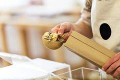 Försäljare som tar pasta från en shoppingpåse i ett organiskt lager royaltyfri foto