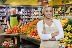 Försäljare Standing Arms Crossed medan kollega som staplar apelsinen arkivfoton