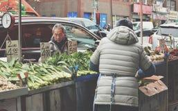 Försäljaren för NYC-kineskvarterfrukt står kinesiskt folk som säljer den gatafrukter och grönsaken fotografering för bildbyråer