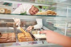 Försäljaren i bagerit som ut tar kexet med kräm från, ställer ut Arkivfoton