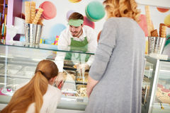 Försäljaren i konfekt tjänar som flickan med glass Royaltyfria Foton
