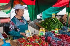 Försäljaren som säljer bär i grönsakmässa Royaltyfri Bild