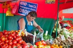 Försäljaren som säljer frukt i grönsakmässa Royaltyfri Foto