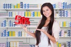 FörsäljareShowing 50% tecken på supermarket Royaltyfri Bild