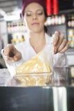 FörsäljareWrapping Cheese In livsmedelsbutik Royaltyfria Bilder