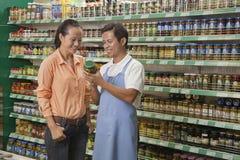 Försäljningar är kontorist att hjälpa kvinnor som undersöker kruset i supermarket, Peking arkivbild
