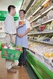 Försäljningar är kontorist att hjälpa mannen i supermarket, Peking royaltyfria bilder